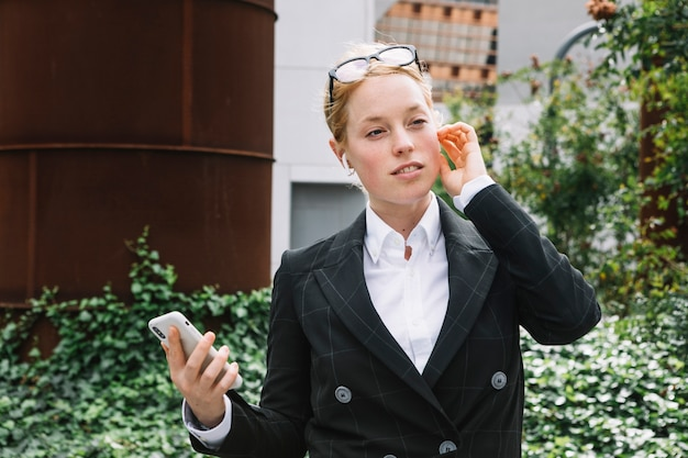 ブルートゥースを聞いて手に携帯電話を保持している若い実業家の肖像画