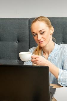 카페에서 커피 한잔과 함께 테이블에 앉아 노트북을 사용하는 젊은 사업가의 초상화