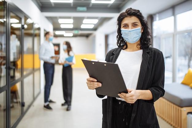 사무실 복도에서 서류 및 비즈니스 동향과 전망을 확인하는 의료 마스크를 쓰고 젊은 사업가의 초상화.