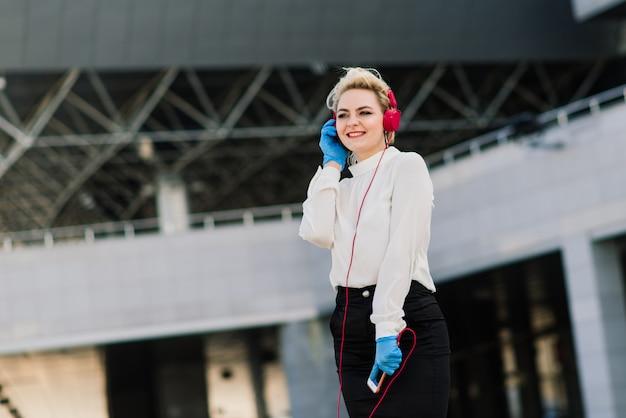 電話、ノートブック、タブレット、コーヒーを屋外で若い実業家の肖像画。青いゴム手袋でブロンドの女の子。