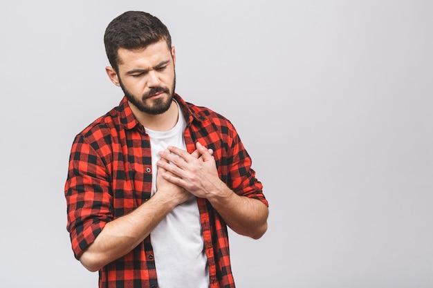 Портрет молодого вскользь человека стоящего изолированного над белой предпосылкой, имеющего сердечный приступ. боль в сердце.