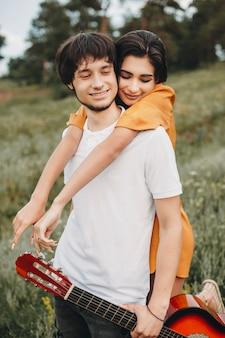 Портрет молодой кавказской пары знакомств на открытом воздухе, пока мужчина держит гитару, а девушка обнимает его сзади.