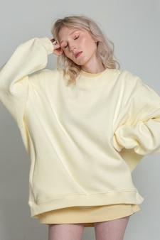 白い背景の上の特大のパーカーで若い白人の夢のような金髪の女性の肖像画