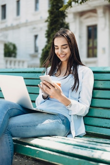 그녀의 다리에 노트북과 함께 해변에 밖에 앉아있는 동안 웃 고 그녀의 스마트 폰보고 길고 검은 머리를 가진 젊은 백인 여자의 초상화.