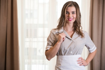 Portrait of a young chambermaid holding her collar standing in the hotel room