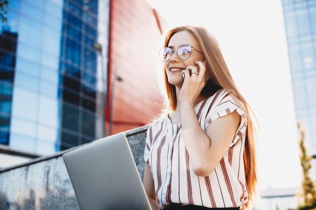 외부 그녀의 다리에 노트북을 들고 그녀의 스마트 폰에서 말하는 젊은 매력적인 비즈니스 여자의 초상화.