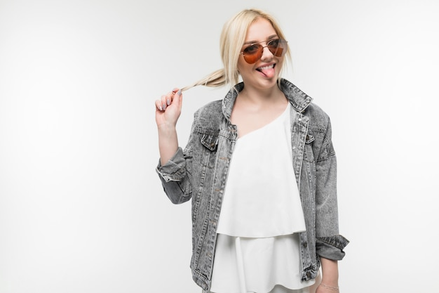Портрет молодой очаровательной радостной блондинки в джинсовой куртке, позирующей и жестикулирующей в круглых очках на белом фоне студии