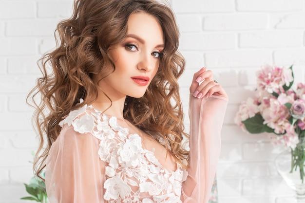 Портрет молодой очаровательной дамы с красивым макияжем и вьющимися волосами