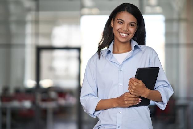 Портрет молодой веселой красивой деловой женщины, держащей цифровой планшет, смотрящей в камеру и