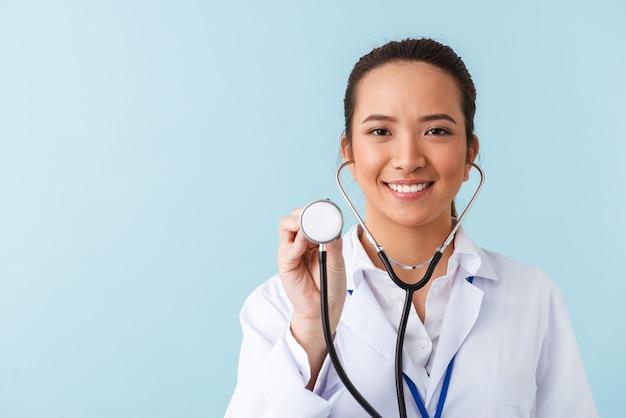 聴診器で青い壁の上に孤立してポーズをとって若い陽気な幸せな女性医師の肖像画。