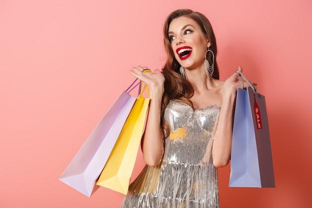 Портрет молодой веселой женщины в ярком платье с блестками, изолированном над розовой стеной, держащей хозяйственные сумки, глядя в сторону.