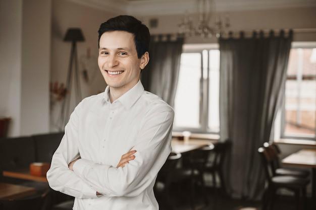 交差した手で彼のレストランに座って、笑顔でカメラを見ている若い自信を持って起業家の肖像画。