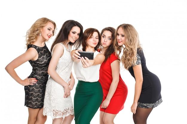 젊은 부부의 유행 여자 금발 머리와 밝은 드레스 포즈와 카메라에 미소 갈색 머리와 스마트 폰 selfi를 만든다