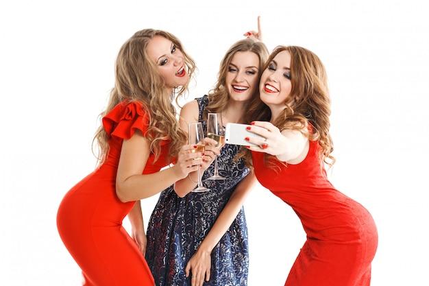 젊은 부부 유행 여자 금발 머리와 밝은 드레스에 갈색 머리의 초상화 포즈와 카메라에 웃 고 스마트 폰 selfi를 만든다