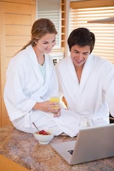 Портрет молодой пары, с завтраком, используя ноутбук