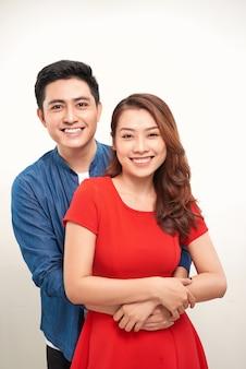 白い背景に抱き締めて立っている若いカップルの肖像画
