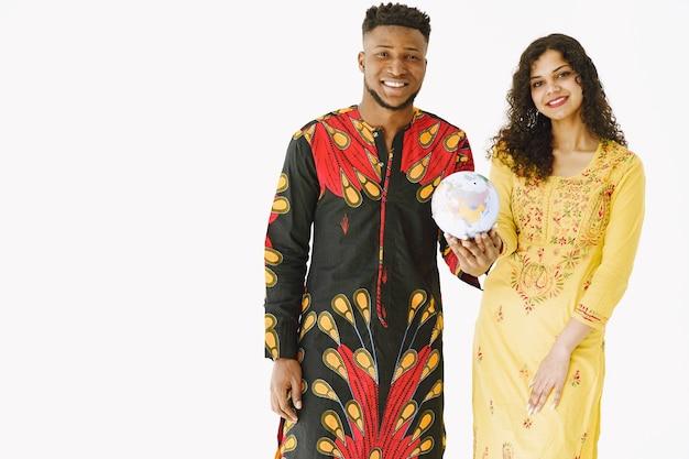 若いカップル、インド人女性、地球儀を持つアフリカ人男性のポートレート。白い背景で隔離。