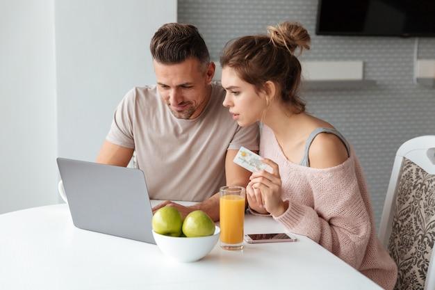 Портрет молодой пары, покупки в интернете с ноутбуком