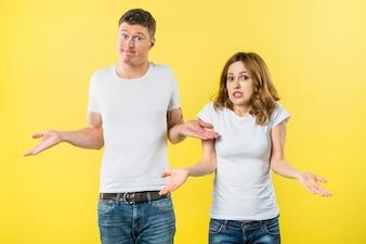 黄色の背景に対して肩をすくめて若いカップルの肖像画