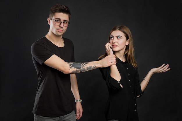 携帯電話で立っている若いカップルの肖像画、黒い背景の上に孤立した近くに立っている欲求不満の男が携帯電話を持っている女の子