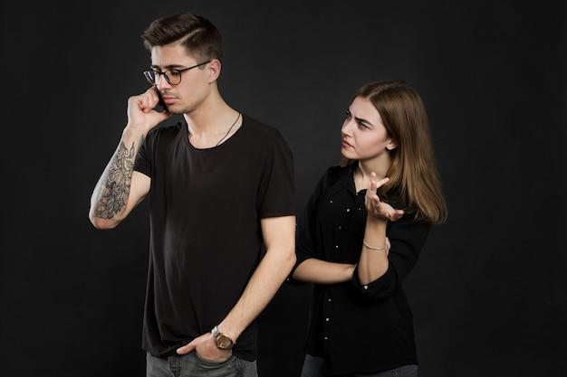 携帯電話で立っている若いカップルの肖像画、男は黒い背景の上に孤立して近くに立っている怒っている女の子が携帯電話を使用しています