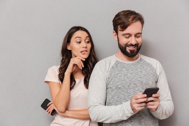 携帯電話を使用して若いカップルの肖像画