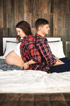 카메라에 포즈를 취하는 아기, 임신 부부를 기다리는 젊은 부부의 초상화.