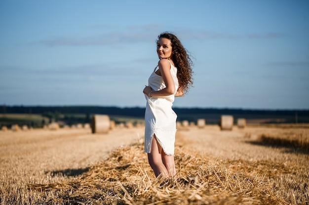 밀이 깎이고 다발이 서 있는 밀밭에 있는 곱슬머리 젊은 여성의 초상화는 자연을 즐기고 있습니다. 자연. 태양 광선 농업