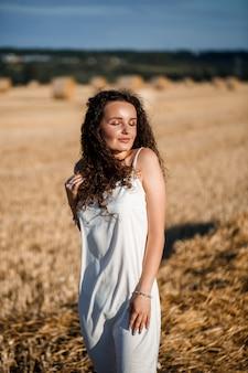 밀밭에 있는 곱슬머리 젊은 여성의 초상화, 밀이 베고 다발이 서서 자연을 즐기고 있습니다. 자연. 태양 광선 농업