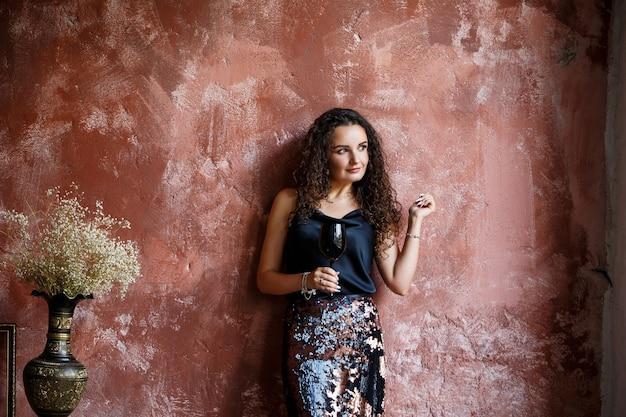 黒のサテンのトップとスカートに身を包んだ赤い壁を背景にヨーロッパ風の若い巻き毛の女性の肖像画