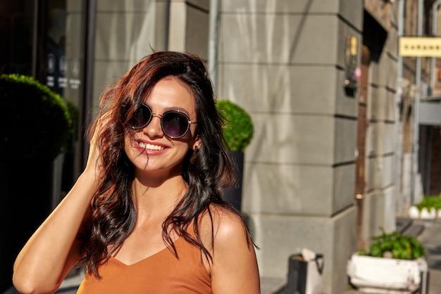 안경을 쓰고 카메라를 보며 웃고 있는 젊은 백인 여성의 초상화는 도시 거리에 서서 좋은 날씨를 즐기고 있습니다. 사람들의 라이프 스타일과 패션 개념
