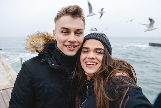 Портрет молодой милой любящей пары, идущей на пляже на открытом воздухе с удовольствием, делает селфи камерой.