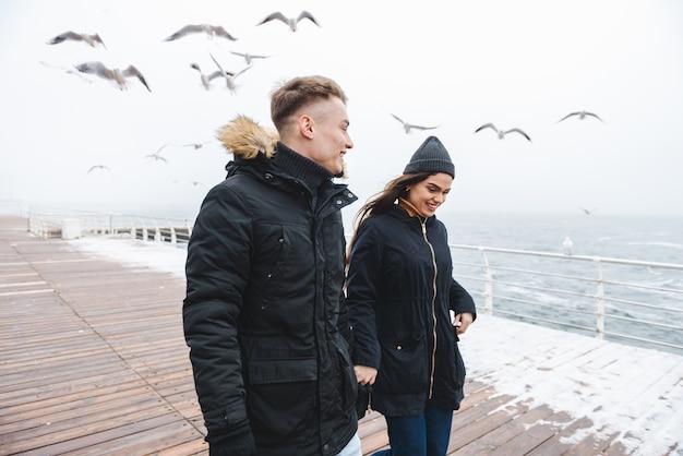 楽しんで屋外のビーチを歩いている若いかわいい愛情のあるカップルの肖像画。
