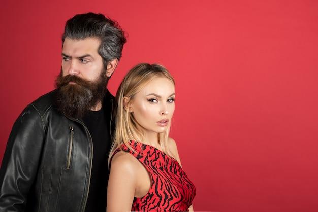 Портрет молодой элегантной пары. чувственная молодая женщина и ее бородатый любовник. пара моды на красном.