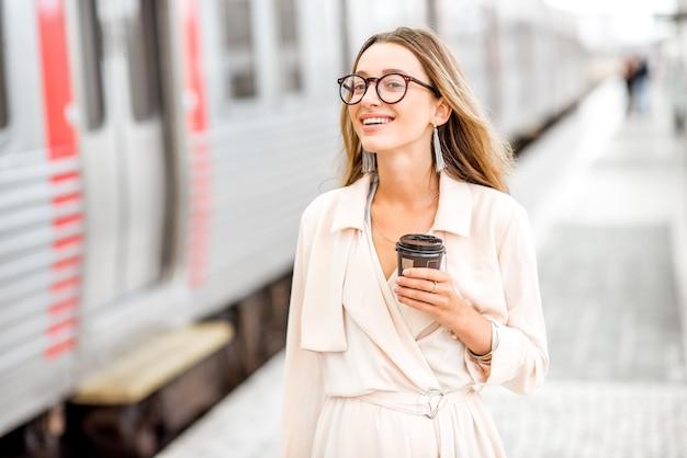 Портрет молодой элегантной женщины, стоящей с чашкой кофе возле поезда на вокзале