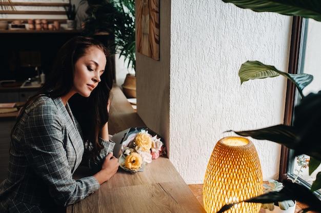 窓の近くに花束が立っているカフェで長い髪の若いヨーロッパの女の子の肖像画、待っているカフェで長い髪のジャケットの背の高い女の子