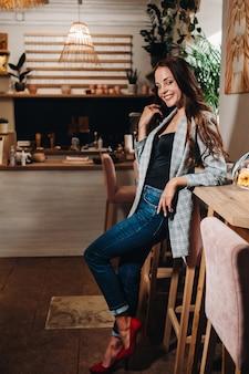 Портрет молодой европейской девушки с длинными волосами в кафе в вечернем свете, высокая девушка в куртке с длинными волосами в кафе.