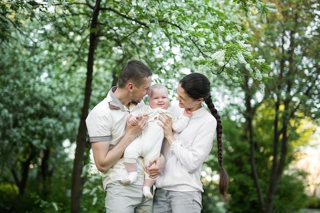 아이와 함께 젊은 가족의 초상화입니다. 여름날 야외에서 시간을 보내는 행복한 젊은 가족. 가족 생활의 행복과 조화. 행복한 가족 개념입니다.