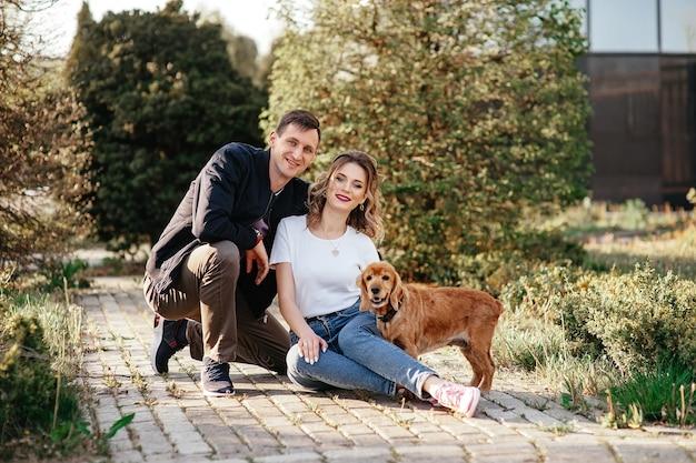 Портрет молодой семьи с собакой в парке