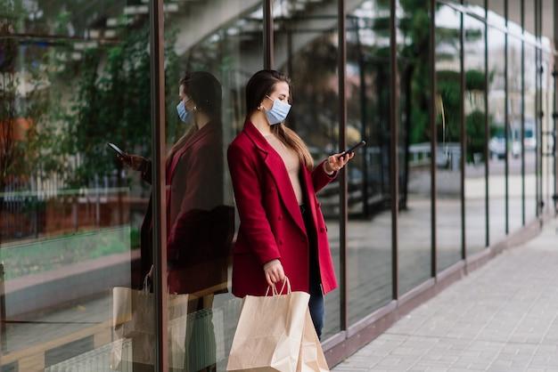 도시 거리에서 쇼핑백과 함께 보호 마스크를 쓴 젊은 패션 여성의 초상화