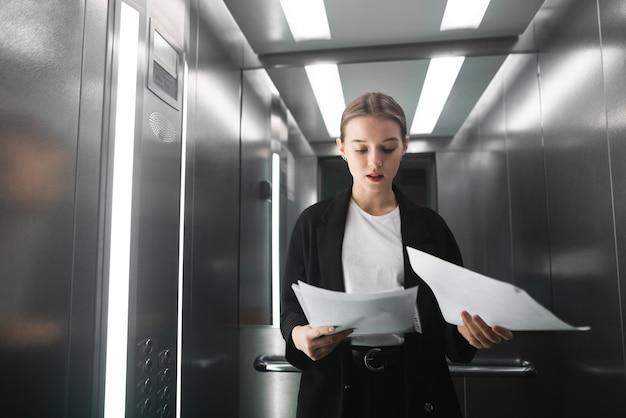 エレベーターに立っている文書を読む若い女性従業員の肖像画