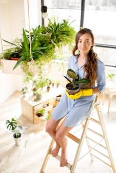 Портрет молодой женщины-садовника с цветочным горшком, сидящей на лестнице в оранжерее