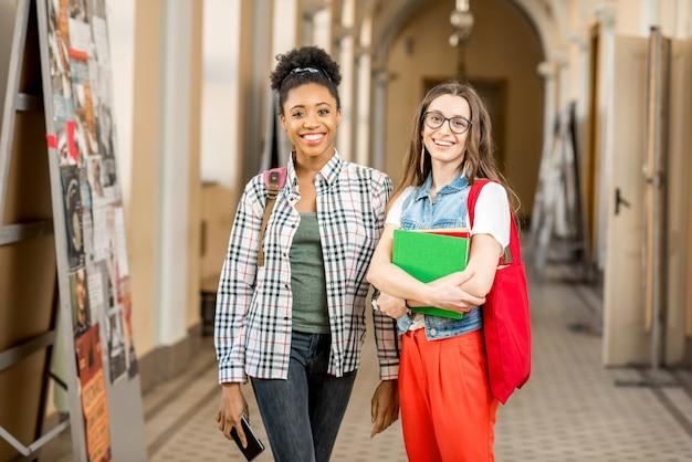 古い大学の廊下で一緒に立っている若い女性の多民族の学生の肖像画
