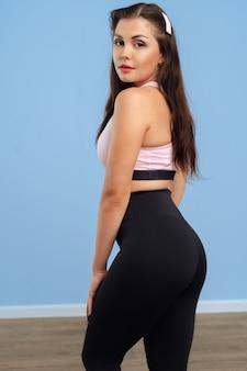 Портрет молодой женщины фитнеса в спортивной одежде, позирующей в студии