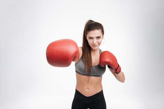 分離されたボクシンググローブで正面をパンチする若いフィットネス女性の肖像画