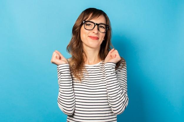 カジュアルなtシャツとメガネの若いフレンドリーな女性の肖像画。感情的な顔。お祝いのジェスチャー