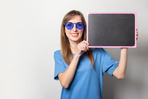 光のテキストのための空白の黒い黒板を保持しているカジュアルな青いtシャツ、青いメガネで笑顔でフレンドリーな若い女性の肖像画。感情的な顔