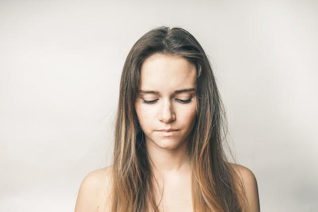 긴 머리를 가진 좌절한 젊은 여성의 초상화, 그녀는 아래를 내려다봅니다