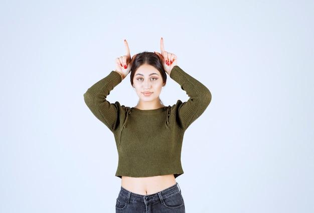 Портрет молодой смешной женщины модельной стоя и показывая уши зайчика пальцами.