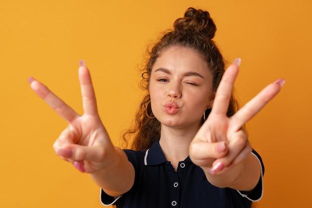 Портрет молодой смешной женщины, показывающей жест мира на желтом фоне